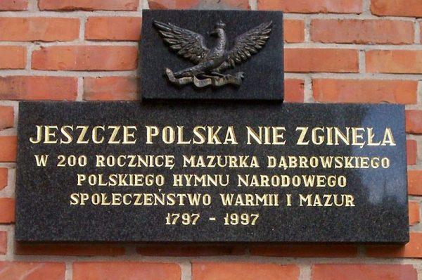 Hymn Polski związany jest z dwoma masonami: Józefem Wybickim , autorem tekstu, i Henrykiem Dąbrowskim, który pojawia się już w tytule. Na zdjęciu tablica pamiątkowa z Olsztyna.