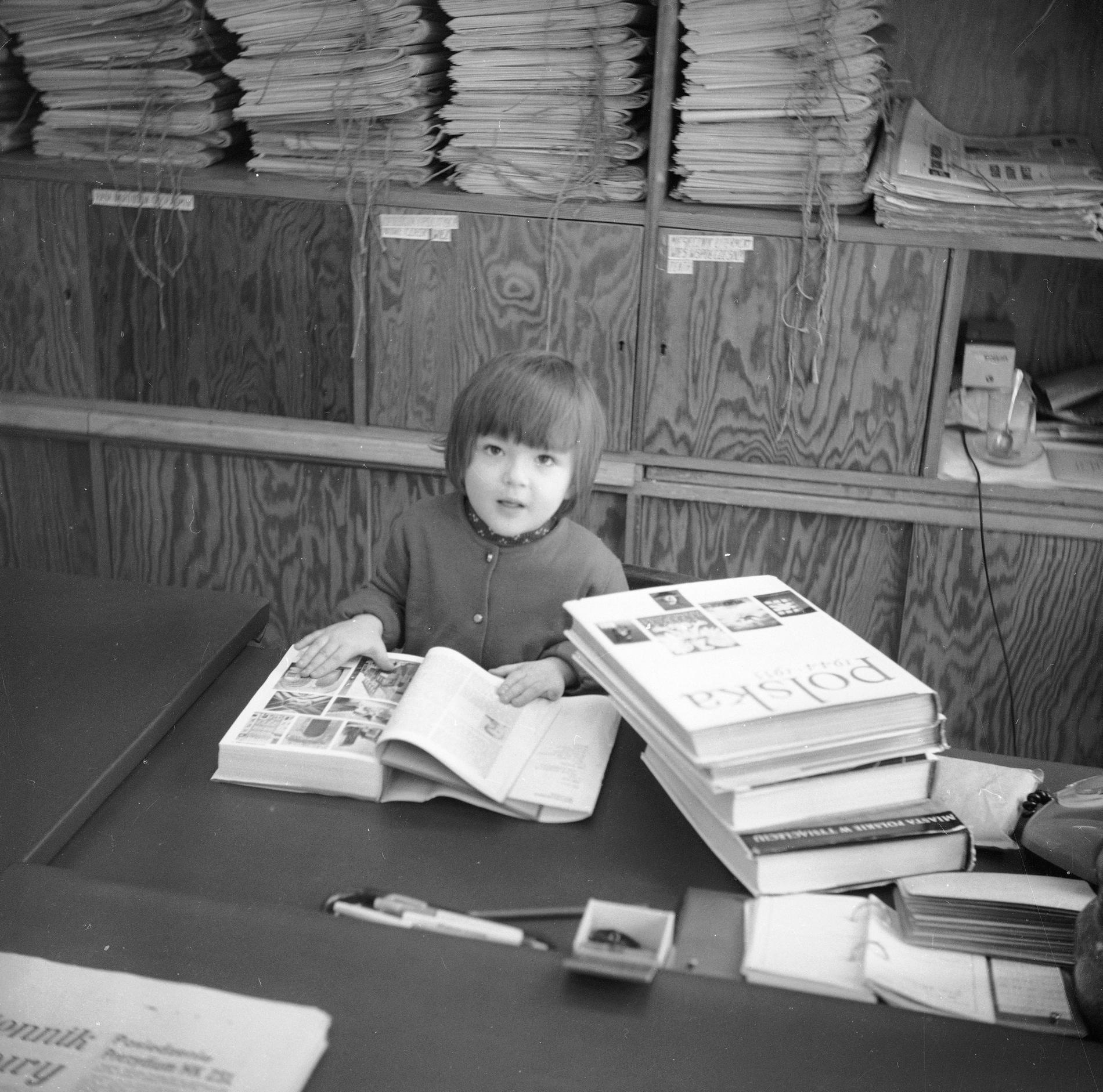 """Dziewczynka czyta książkę przy stole. Widoczne książki - """"Polska 1944-1955"""" i """"Miasta polskie w tysiącleciu""""."""