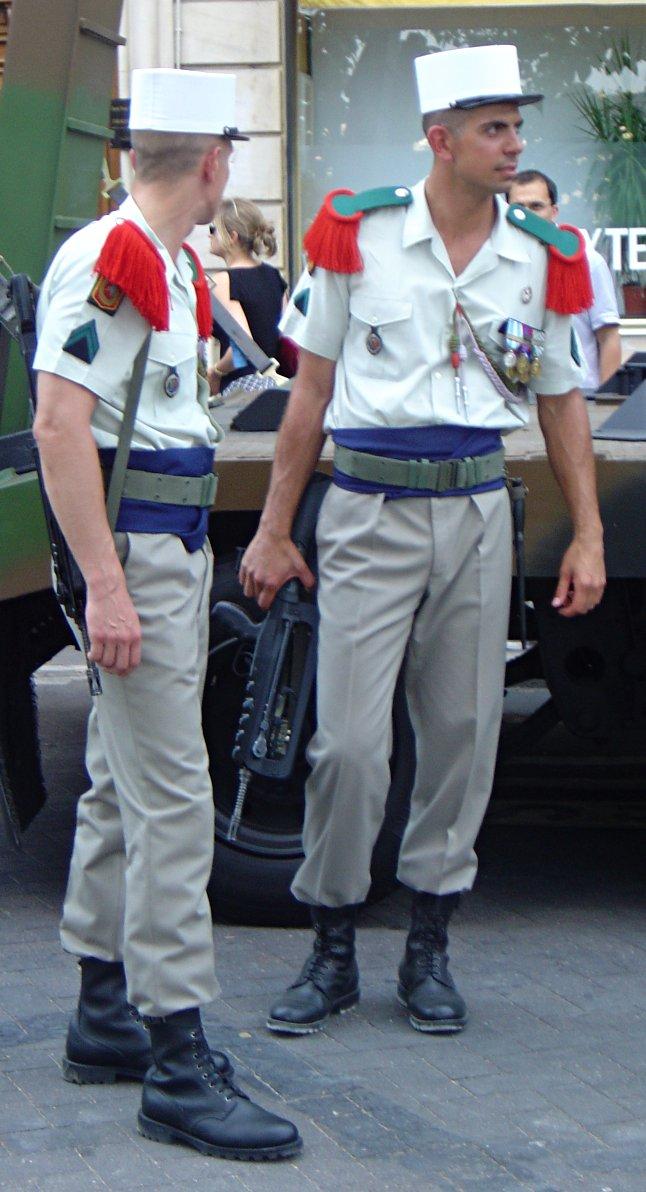 Żołnierze Legii Cudzoziemskiej podczas przerwy w dniu defilady z okazji Święta Narodowego Francji. Czerwone naramienniki oraz białe kepi stanowią charakterystyczne elementy umundurowania tej słynnej formacji. Obowiązkowo - z karabinem FAMAS.