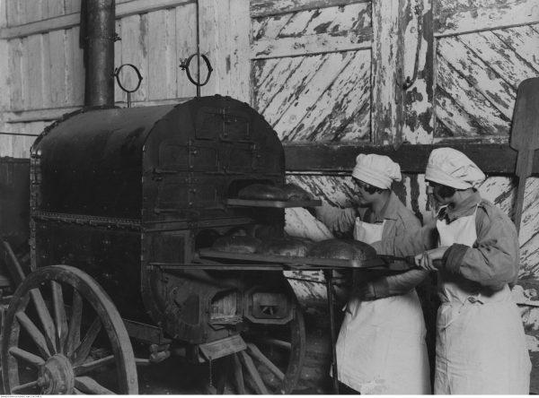 Jak pogodzić pracę z prowadzeniem domu? Przedwojenne kobiety nie pytały, po prostu sobie radziły. Na zdjęciu dziewczęta ze Związku Strzeleckiego podczas pieczenia chleba.