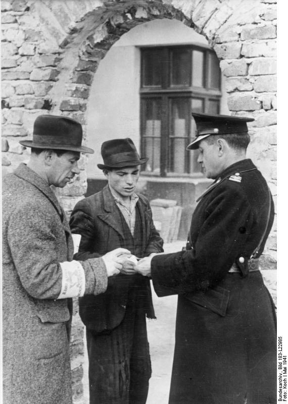 Krakowskie getto powstało w części dzielnicy Podgórze. Otoczono ją drutem kolczastym a następnie wzniesiono wokół powstałego getta wysoki mur. Na zdjęciu jeden z policjantów kontroluje dokumenty w getcie ok. 1941 roku.