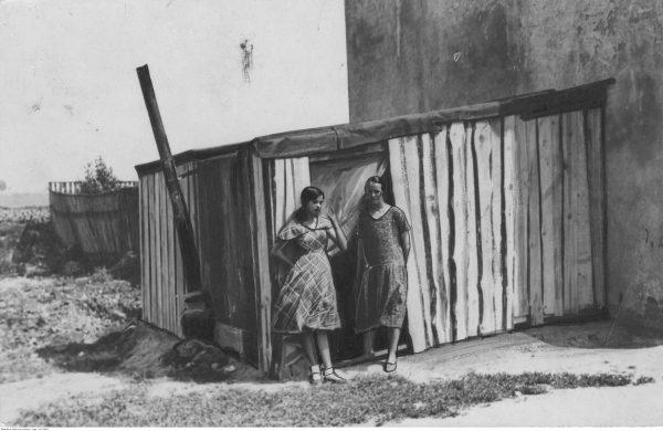 Dwie bezrobotne kobiety przed drewnianą szopą służącą im za mieszkanie. Lata 20.-30.