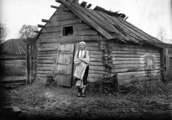 Kobieta z powiatu sarneńskiego obok swojego walącego się domu. Choć dziś nie chcemy o tym pamiętać, ogromne rzesze ludności żyły w skrajnej biedzie. (fot. domena publiczna)