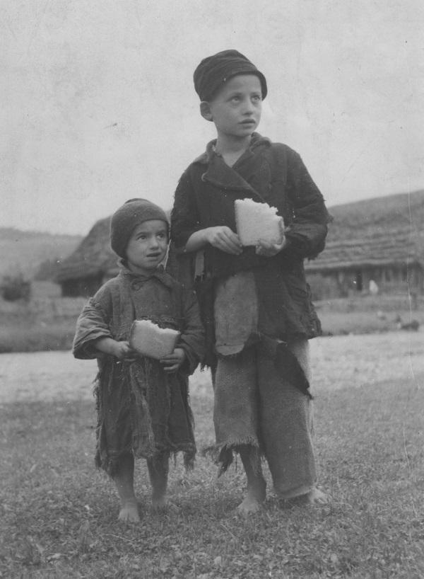 Ubodzy obdarci chłopcy posilający się kromką chleba. (fot. domena publiczna)