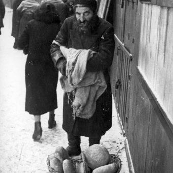 Żyd handlujący chlebem na ulicy. Fotografia z okresu II wojny światowej.