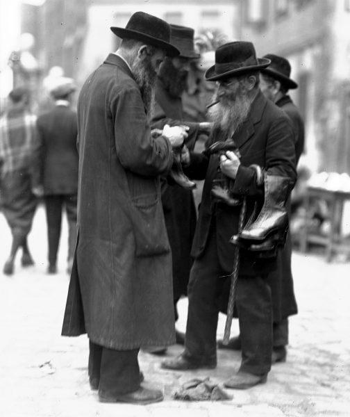 Żyd sprzedający buty na ulicy na krakowskim Kazimierzu. Fotografia przedwojenna.