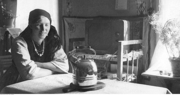 """Wiejska kobieta wpatruje się niepewnie w czajnik elektryczny. Wreszcie aby zagotować wodę na herbatę nie trzeba pędzić po drewno. Ilustracja i podpis pochodzą z książki """"Dwudziestolecie od kuchni"""" Zaprutko-Janickiej."""