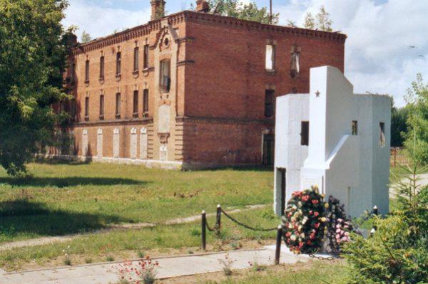 """Pozostałości budynku obozowego w Berezie wraz z pomnikiem upamiętniającym osoby przetrzymywane w """"miejscu odosobnienia""""."""
