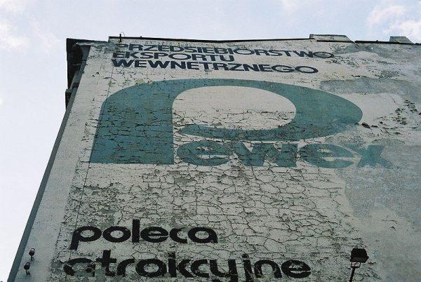 """Słynny """"Pewex"""", czyli przedsiębiorstwo państwowe z siedzibą w Warszawie, prowadziło sieć sklepów i kiosków walutowych w PRL. W tamtych czasach marka ta była synonimem towarów luksusowych. Na zdjęciu reklama """"Pewexu"""" na jednym z budynku w Łodzi."""