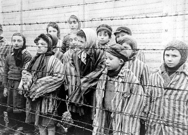 Dzieci za drutami obozu. Zdjęcie stanowi kadr z sowieckiego filmu dokumentującego wyzwolenie Auschwitz.