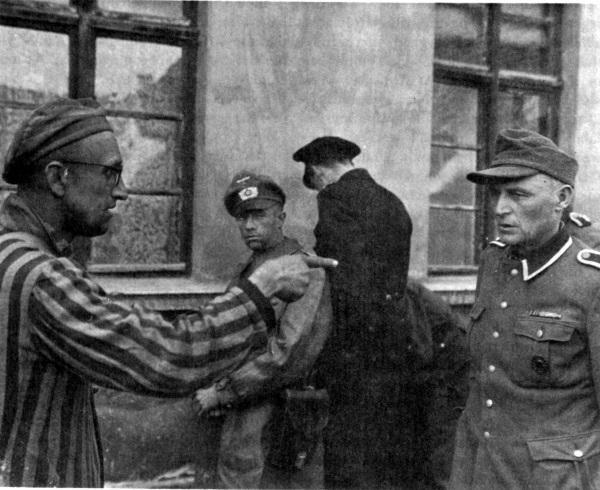Ocalony z Buchenwaldu wskazuje palcem obozowego strażnika, który znany był z brutalności względem więźniów (fot. domena publiczna)