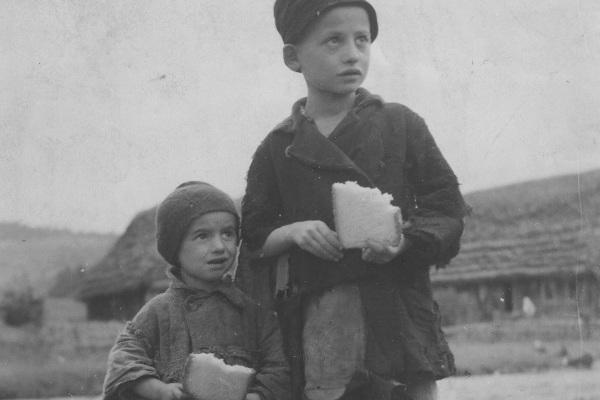 Ubodzy chłopcy posilający się kromką chleba.