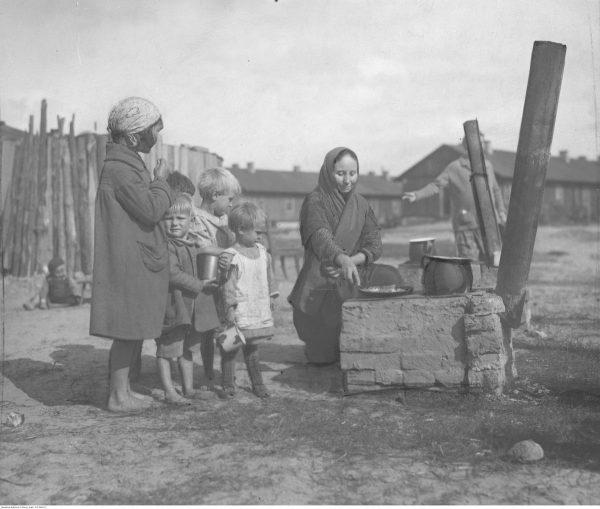 Bieda i głód. Taka była codzienność większości mieszkańców przedwojennej wsi. Na zdjęciu grupa dzieci z Żoliborza przy prowizorycznej kuchni, na której kobieta przyrządza posiłek.
