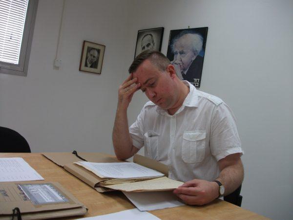 Prof. Łukasz Tomasz Sroka na fotografii wykonanej w archiwum w Tel Awiwie. W tle widoczny portret Ben Guriona.