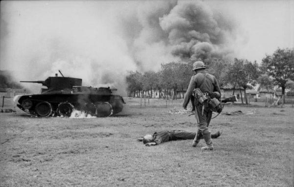 Niemiecki żołnierz spogląda na zabitego radzieckiego żołnierza i zniszczony czołg BT-7.