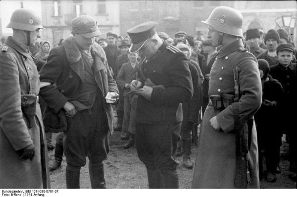 """""""Granatowi"""", tak potocznie nazywano polską policję podporządkowaną lokalnym komendantom niemieckiej policji porządkowej. Na zdjęciu granatowy policjant sprawdzający dokumenty (1941 rok)."""
