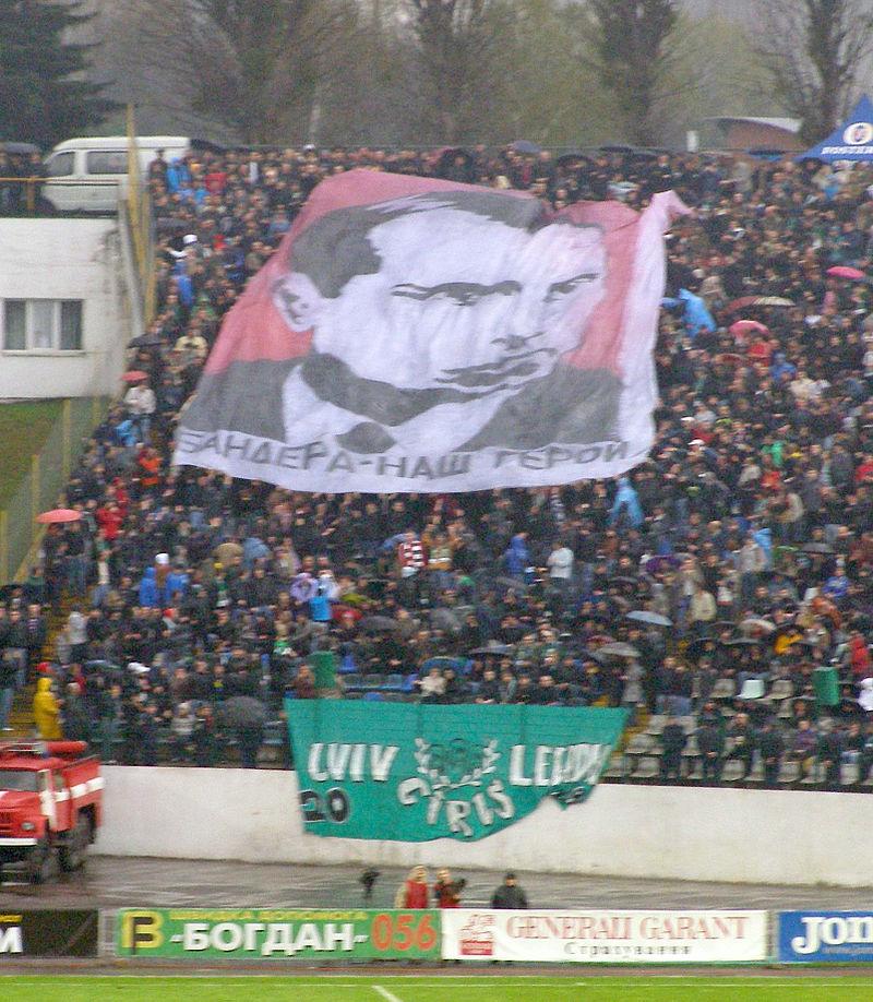"""Dosłowny kult Bandery jako bohatera narodowego eksplodował po 1989 roku. Na zdjęciu Sektorówka kibiców Karpat Lwów, przedstawiająca wizerunek Stepana Bandery z napisem """"Bandera – nasz bohater"""", podczas meczu z Szachtarem Donieck (15 kwietnia 2010)."""
