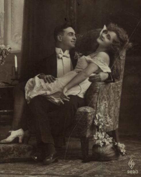 Mężczyzna w fotelu i kobieta siedząca na jego kolanach. Pocztówka z początku XX wieku