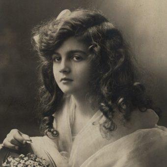 Dziewczyna z koszyczkiem kwiatków. Fotografia z początku XX wieku