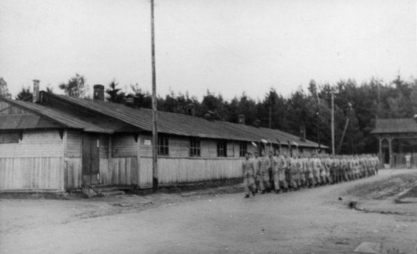 Grupa robotników z łopatami na ramionach w drodze do pracy na terenie nierozpoznanego obozu Służby Budowlanej Baudienst.