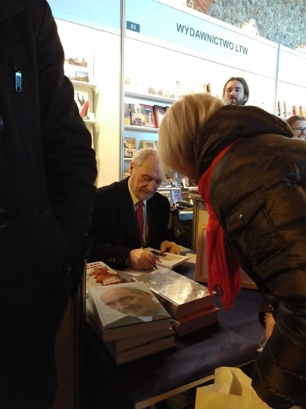 Antoni Macierewicz podpisuje swoje książki. Po lewej ramię jego groźnie wyglądającego ochroniarza. Całej sylwetki nie odważyliśmy się uchwycić w kadrze (fot. Aleksandra Zaprutko-Janicka)