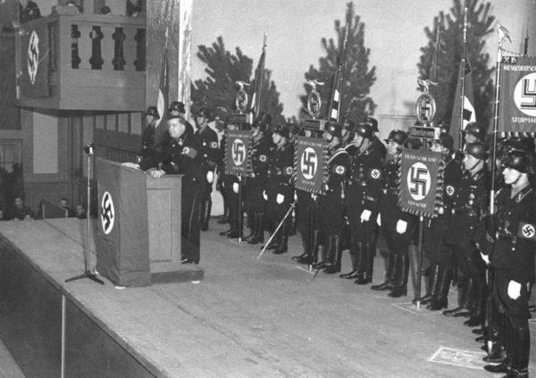 """Książka Hitlera stała się swego rodzaju Biblią dla nazistów. Zdjęcie z wykładu SS-Hauptsturmführera Walthera Wüsta pod hasłem: """"Mein Kampf"""" jako lustro aryjskich poglądów."""