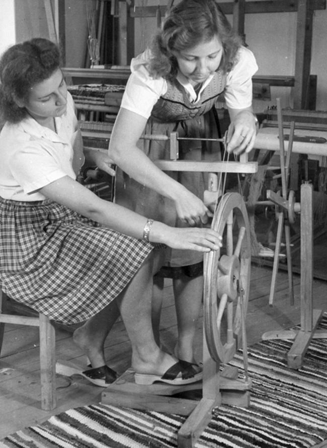 Kobiety przy kołowrotku. Obie mają starannie ułożone fryzury. Ta, która siedzi, ma na nogach buty na drewnianej podeszwie ze skórzanymi paskami (fot. domena publiczna)