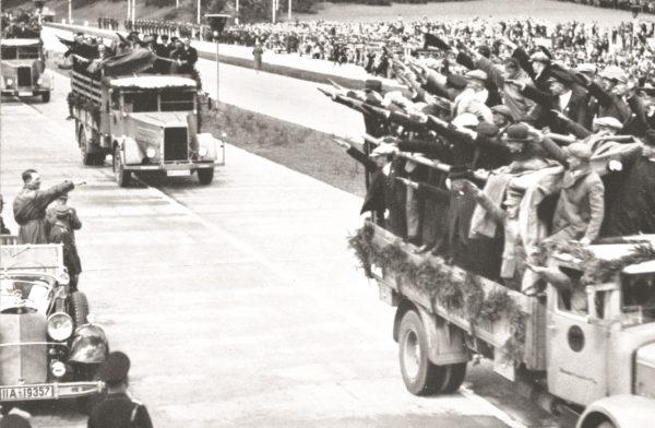 Hitler wymienia niemieckie pozdrowienie z grupą robotników podczas otwarcia odcinka autostrady.