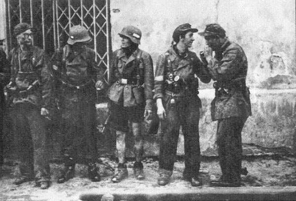 """Żołnierze batalionu """"Miotła"""" po ewakuacji kanałami do Śródmieścia w okolicach włazu kanałowego przy ul. Wareckiej."""