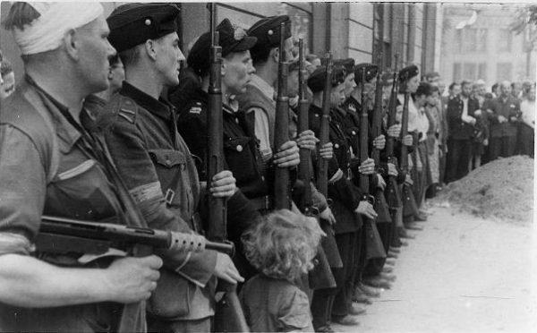 """Powstańcy niemal codziennie stykali się ze śmiercią, także bliskich sobie osób. Na zdjęciu pogrzeb powstańczy w batalionie """"Kiliński""""."""